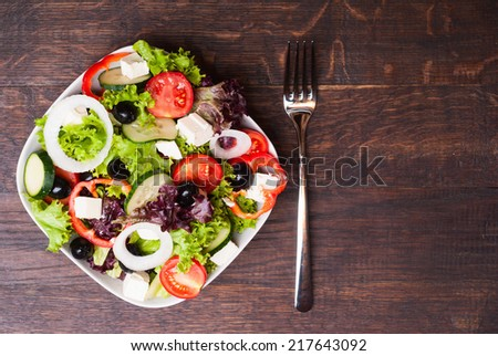 Greek salad on wooden background - stock photo