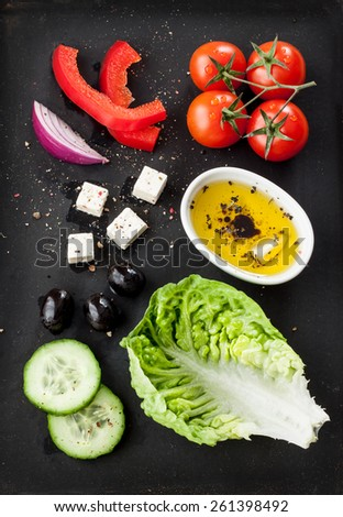 Greek salad recipe ingredients on black chalkboard from above. Feta cheese, cherry tomatoes, onion, cucumber, olives, lettuce, red pepper and olive oil.  - stock photo