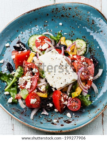 Greek salad with feta cheese and sun-dried olives on blue background - stock photo