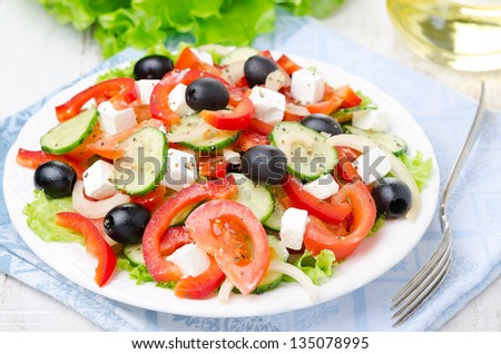 Greek salad with feta cheese, olives and vegetables on a plate, horizontal