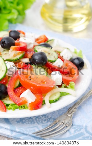 Greek salad with feta cheese, olives and vegetables on a plate, selective focus