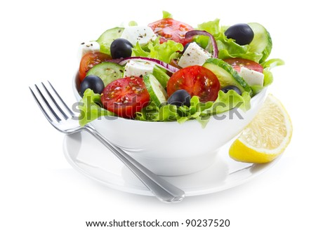 greek salad with fresh vegetables and feta cheese on white background - stock photo