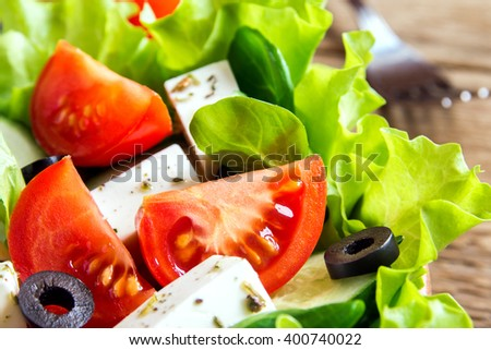 Greek salad with fresh vegetables, feta cheese and black olives close up - stock photo