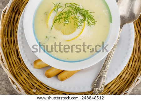 Greek soup avgolemono with a circle of lemon on a white plate on a wicker tray and wooden background with German silver spoon and bread sticks - stock photo