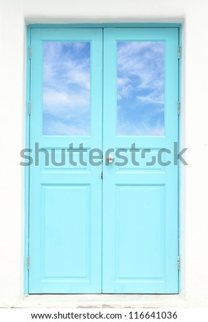 Greek style door with blue sky view - stock photo