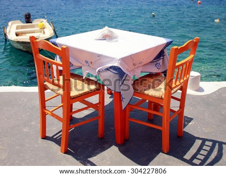 greek tavern with orange wooden chairs by the sea coast, Greece, Santorini island in Cyclades - stock photo