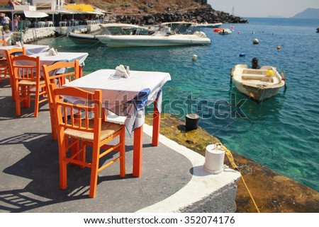 Greek tavern with orange wooden chairs by the sea coast, Greece, Santorini island in Cyclades. Selective focus - stock photo
