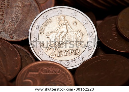 Greek two euros coin among  coins of five cents, representing the abduction of Europe (from Greek Mythology) - stock photo