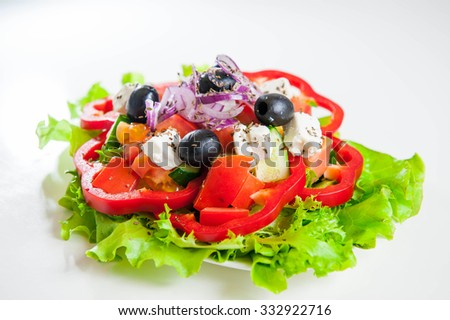 Greek Vegetable salad with feta cheese, olives, cucumbers, tomatoes, pepper  on the white background isolated  - stock photo