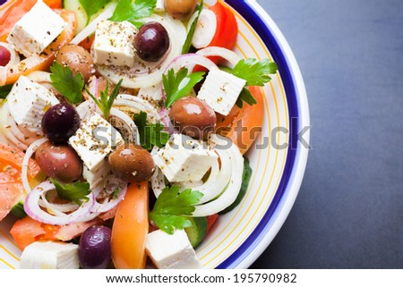 Greek vegetable salad with tomato, onion, cucumber, parsley, olives and feta cheese