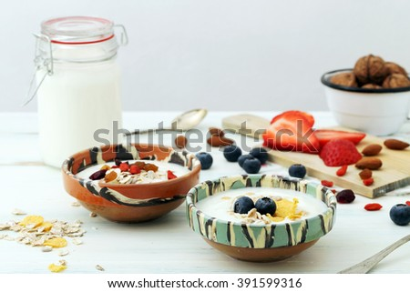 greek yogurt and fresh berries in rustic bowl on kitchen table - stock photo