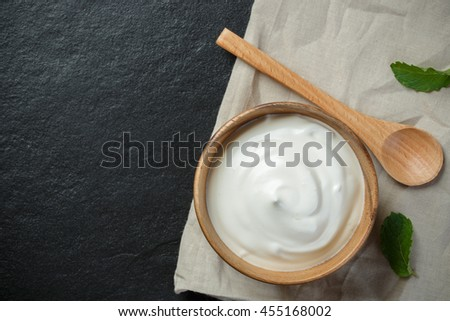 Greek yogurt in a wooden bowl with spoons on stone background - stock photo