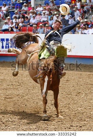 GREELEY, CO - JULY 4:  Top-ranked PRCA bareback cowboy Royce Ford successfully rides in the championship round at the Greeley Stampede, the worlds largest Fourth of July rodeo, on July 04, 2009  in Greeley, CO.. - stock photo