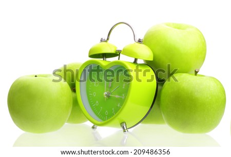 Green alarm clock and apples isolated on white background.