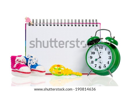 Green alarm clock with  baby boots, isolated on white background - stock photo