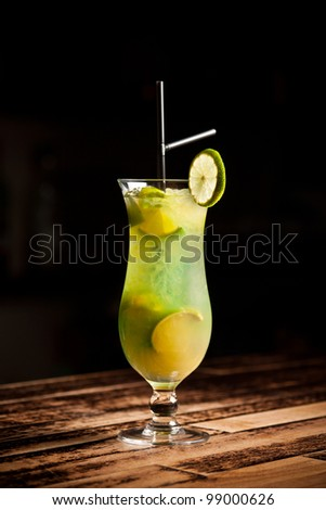 Green alcoholic cocktail with lime on white background