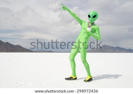 Green alien track star athlete wearing gold medal celebrating with lightning bolt pose on stark white planet background - stock photo