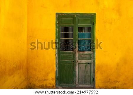 green ancient wooden door on yellow wall - stock photo