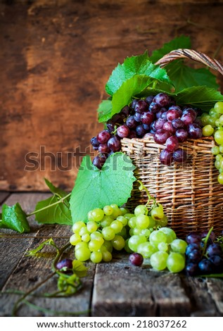Green and Black Grapes in Country Style Basket, on Wooden Table, Selective Focus - stock photo