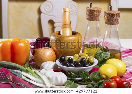 Green and black olives in a bowl, spicy olive oil in glass bottles with dispenser, wooden mortar and pestle, lemon, garlic, basil, bell peppers, tomatoes, onion and spring onion placed on the table. - stock photo