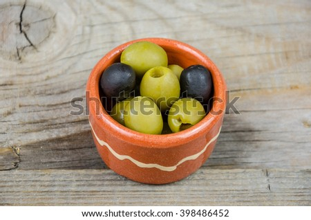 Green and black olives in a clay pot on a wooden table - stock photo
