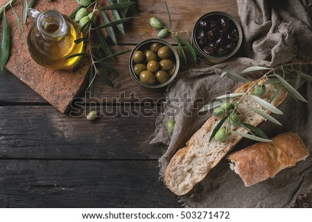 Green and black olives in tin cans with loaf of fresh bread and young olives branch on sackcloth, bottle of olive oil on clay board over old wood background. Overhead view with space for text
