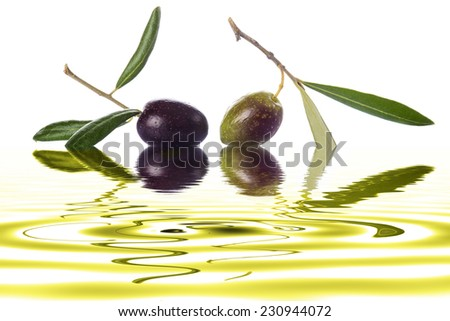 Green and black olives with leaves on its branch to make olive oil on a white background with liquid reflections - stock photo