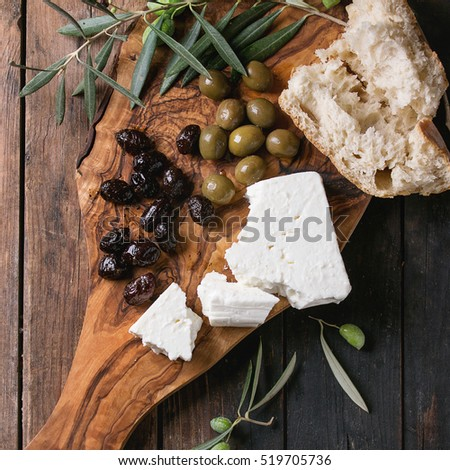 Green and black olives with loaf of fresh bread, feta cheese and young olives branch on olive wood chopping board over old wood background. Overhead view. Square image