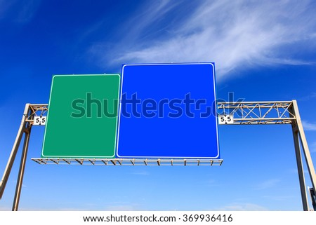 Green and blue highway signs with blue sky in the background