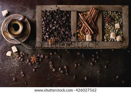 Green and brown decaf unroasted and black roasted coffee beans with spices and sugar in old wooden box, and ceramic cup of fresh making coffee over dark brown textured background. Top view - stock photo