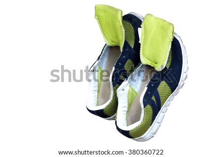green and deep blue canvas shoes drying lean against background with opening shoes tongues (Isolated mode and have clipping path) - stock photo