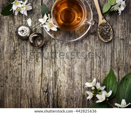 Green and jasmine tea cup on vintage wooden table - stock photo