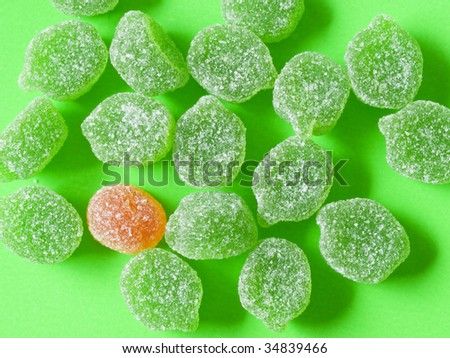 green and one orange candy on green background and green shadows - stock photo