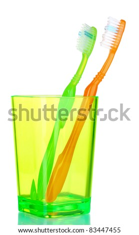 green and orange toothbrushes in glass isolated on white - stock photo
