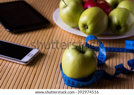 Green and red Apples are on a plate on light bamboo table. Nearby is tablet computer, mobile phone and measuring tape