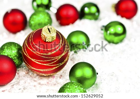 Green and red Christmas balls on white/snow background - stock photo