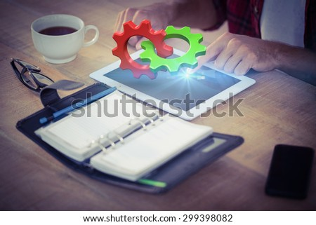 Green and red cog and wheel against creative businessman using a tablet - stock photo