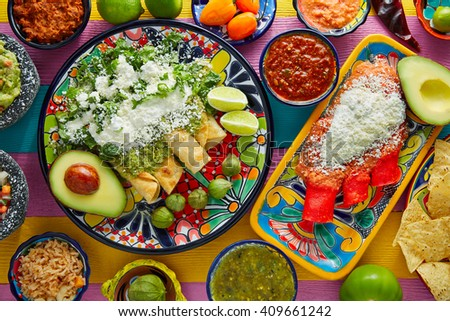 Green and red enchiladas with mexican sauces mix in colorful table - stock photo