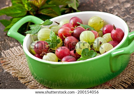green and red gooseberries in a bowl - stock photo