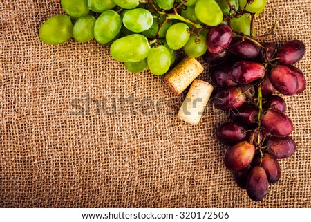 Green and red grape on burlap background, shallow focus.