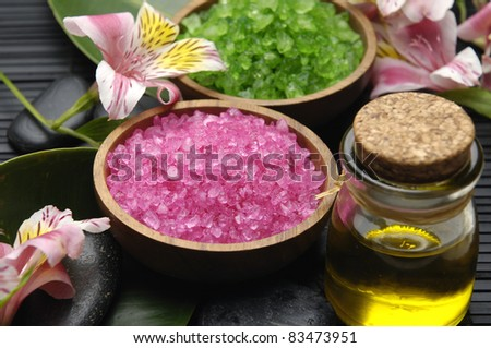 Green and red herbal salt in bowl with zen stone and leaf with massage oil set for spa - stock photo