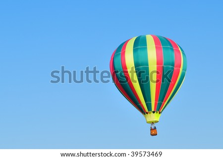 Green and red hot air balloon against a blue sky. - stock photo