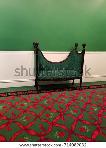 green and red themed room with a green velvet loveseat couch and a dark green carpet