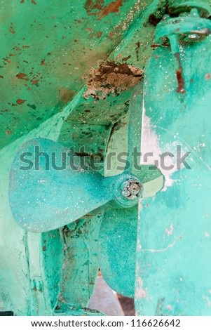 Green and rusty boat propeller - stock photo