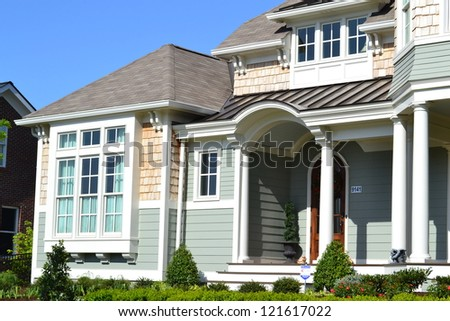 Green and Tan Suburban American Cape Cod Home with Large Front Porch - stock photo