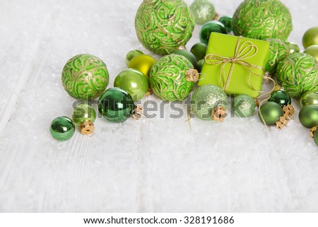 Green and white christmas background with gift box, snow and balls for decoration items. - stock photo