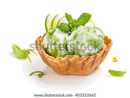 Green and white ice cream with slices of lime fruit in a  wafer bowl decorated with zest isolated on white background. Selective focus on the mint. - stock photo