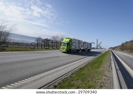 green and white truck on the move, scenic highway and sea, wide angle - stock photo