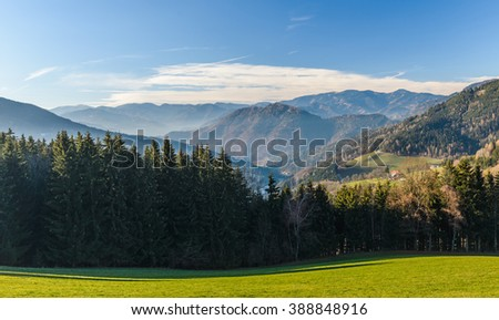 Green and yellow blooming meadow set amid idyllic mountain landscape with dramatic stormy sky. Nature concept of spring and summer in the italian austrian Alps.  - stock photo