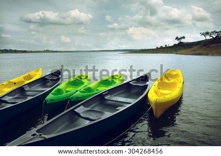 Green and yellow kayaks and canoes docked in the shore of a lake - stock photo